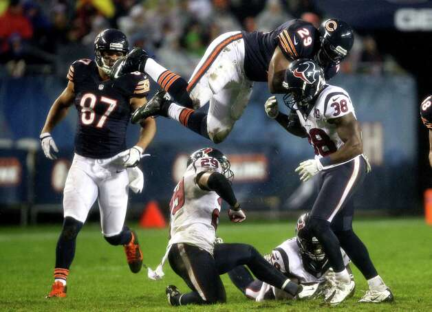 Chicago Bears running back Michael Bush (29) leaps over as Houston Texans safeties Glover Quin (29) and Danieal Manning (38) try to tackle him in the second half of an NFL football game, Sunday, Nov. 11, 2012, in Chicago. Bush was able to run for a few more yards on the play. (AP Photo/Nam Y. Huh) Photo: Nam Y. Huh, Associated Press / AP