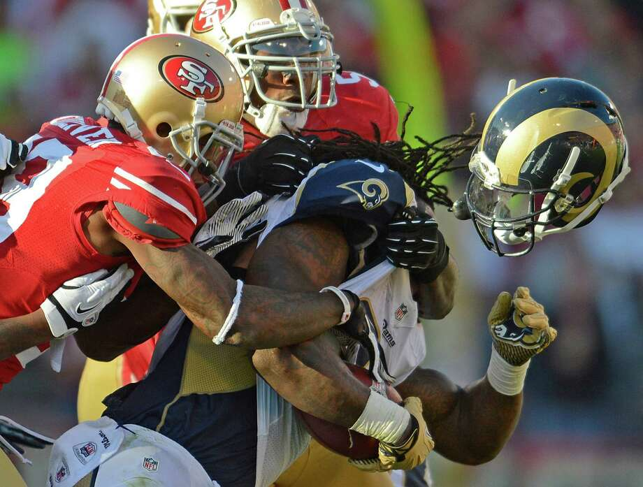 49rs linebacker San Francisco's Patrick Willis, back, separates Rams running back Steven Jackson from his helmet in the third quarter of Sunday's game that ended in a 24-24 overtime tie. Photo: Jose Carlos Fajardo, MBR / Contra Costa Times