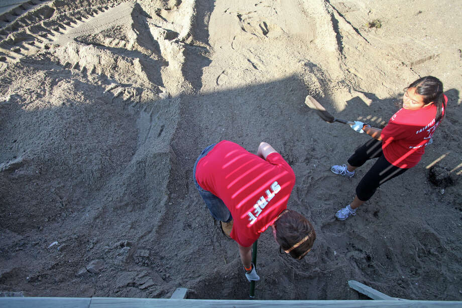 Volunteers and Fairfield Alumni, Mathew Murphy,  of New York, left, and Eliza Carandang, of Bridgeport, remove sand from a home on Fairfield Beach Road in Fairfield, Conn. on Sunday, November 11, 2012. Photo: BK Angeletti, B.K. Angeletti / Connecticut Post freelance B.K. Angeletti