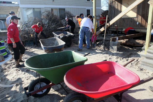 Volunteers remove sand from homes in Fairfield, Conn. on Sunday, November 11, 2012. They were part of a effort of 1000 volunteers to help residents after storm Sandy. Photo: BK Angeletti, B.K. Angeletti / Connecticut Post freelance B.K. Angeletti