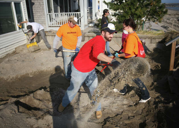 Rob Williams, center, of Norwalk, clears sand from behind a home as part of a large volunteer beach cleanup effort on Fairfield Beach Road in Fairfield on Sunday, November 11, 2012. Photo: Brian A. Pounds / Connecticut Post