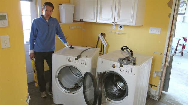 Harbor Road resident Peter Faigl in his ground floor laundry room with his ruined washer and dryer, and walls he peeled back in places to dry out after Hurricane Sandy flood waters.  Westport Ct 11/10/12 Photo: Mike Lauterborn / Westport News contributed