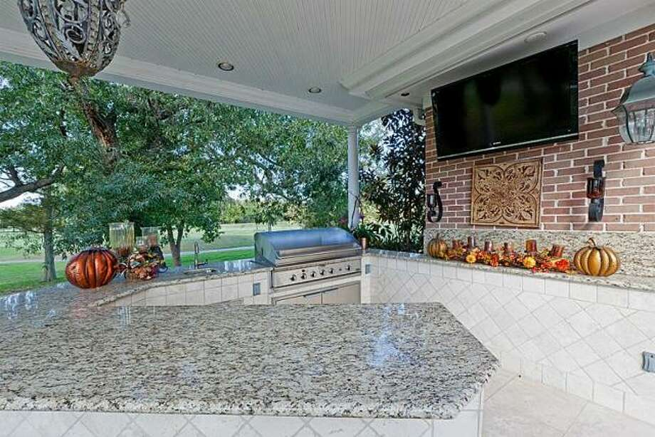 The patio is completely covered and includes an outdoor kitchen. Photo: Better Homes And Gardens Gary Greene