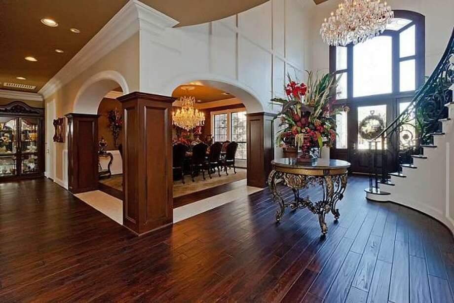 The formal dining room has elegant pillars and an exquisite chandelier. Photo: Better Homes And Gardens Gary Greene
