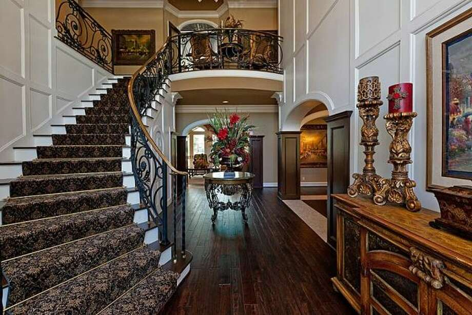 A grand staircase leads to the upper level, which includes a balcony that overlooks the foyer. Photo: Better Homes And Gardens Gary Greene