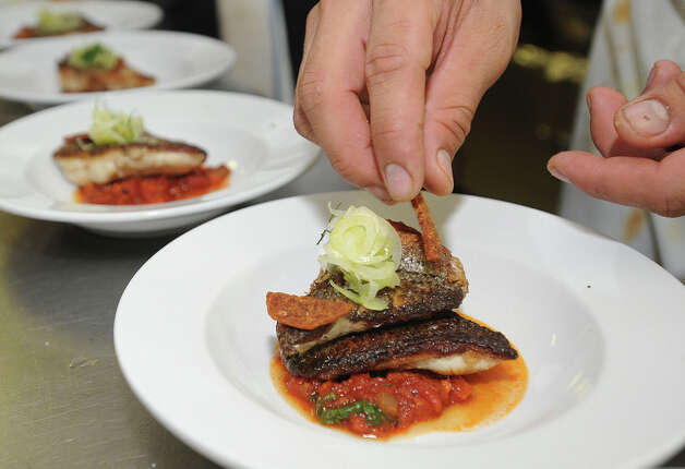 Finsihing touches are added to the crispy striped bass at Tiffany Derry's pop-up restaurant Friday night. Photo taken Friday, November 9, 2012 Guiseppe Barranco/The Enterprise Photo: Guiseppe Barranco, STAFF PHOTOGRAPHER / The Beaumont Enterprise