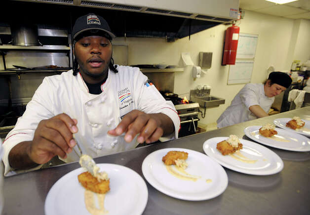 Brandon Portis prepares fried green tomatoes at Tiffany Derry's pop-up restaurant on Friday. Photo taken Friday, November 9, 2012 Guiseppe Barranco/The Enterprise Photo: Guiseppe Barranco, STAFF PHOTOGRAPHER / The Beaumont Enterprise