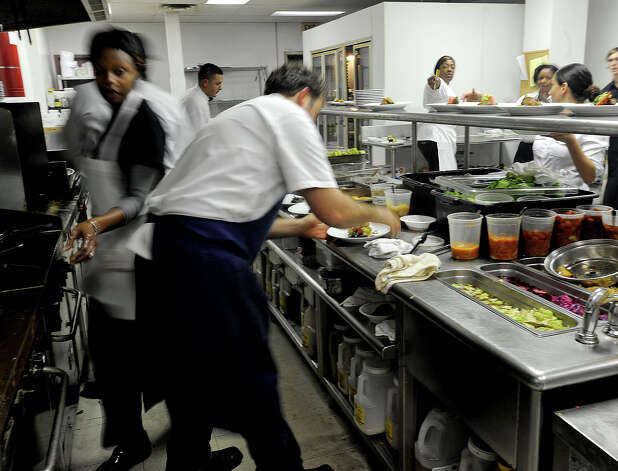Organized chaos in the kitchen. Chefs prepare food while runners and waiters gather dishes to be served. Tiffany Derry can be seen orchestrating efforts. Photo taken Friday, November 9, 2012 Guiseppe Barranco/The Enterprise Photo: Guiseppe Barranco, STAFF PHOTOGRAPHER / The Beaumont Enterprise