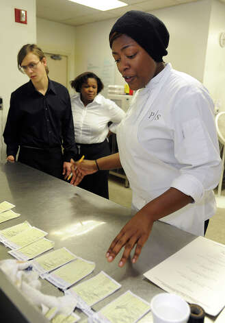Tiffany Derry looks over orders in the kitchen at Derry's pop-up restaurant on Friday. Matthew Parrish and Mary Brown serve food. Photo taken Friday, November 9, 2012 Guiseppe Barranco/The Enterprise Photo: Guiseppe Barranco, STAFF PHOTOGRAPHER / The Beaumont Enterprise