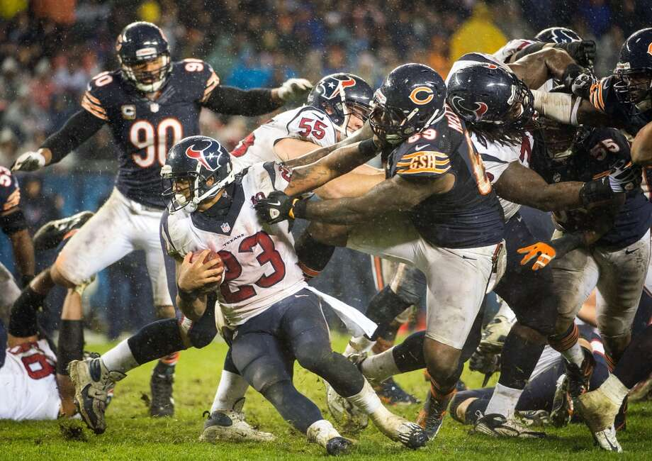 Houston Texans running back Arian Foster (23) tries to get away from Chicago Bears defensive tackle Henry Melton (69) during the fourth quarter at Soldier Field on Sunday, Nov. 11, 2012, in Chicago. In the rain and mud, Foster ran for 102 yard as the Texans won 13-6. (Smiley N. Pool / Houston Chronicle)