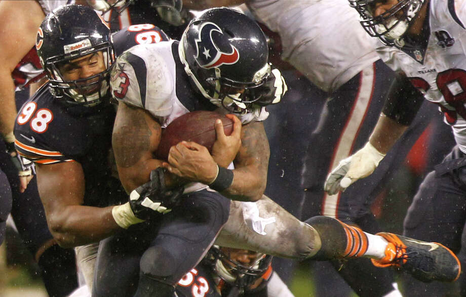 Bears defensive end Corey Wootton (98) tackles Texans running back Arian Foster (23), grabbing his face mask for a 15-yard penalty during the fourth quarter. Photo: Brett Coomer, Houston Chronicle / © 2012  Houston Chronicle