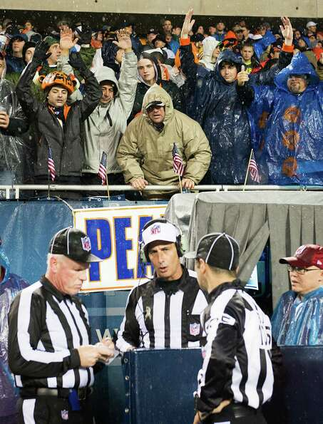 Bears fans yell for a call from referee Gene Steratore as he visits the instant replay booth during
