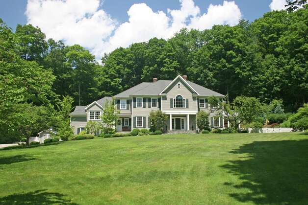"This 11-room Colonial at 31 Bernhard Drive, Weston, sits on a 2.27-acre parcel on a quiet cul-de-sac, abutting the Aspetuck Land Trust open space ""Crow Hill Nature Preserve"" and Trout Brook Valley. Photo: Contributed Photo"