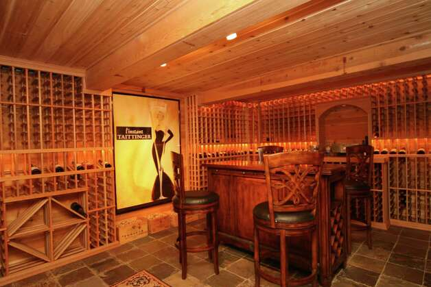 This 2,000-plus bottle climate-controlled wine cellar on the basement level features a stone entrance, Malaysian mahogany hardwood racks and a slate floor. Photo: Contributed Photo