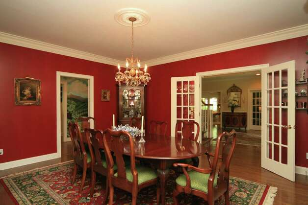 The formal dining room features an ornate chandelier hanging gracefully from a ceiling medallion. Photo: Contributed Photo