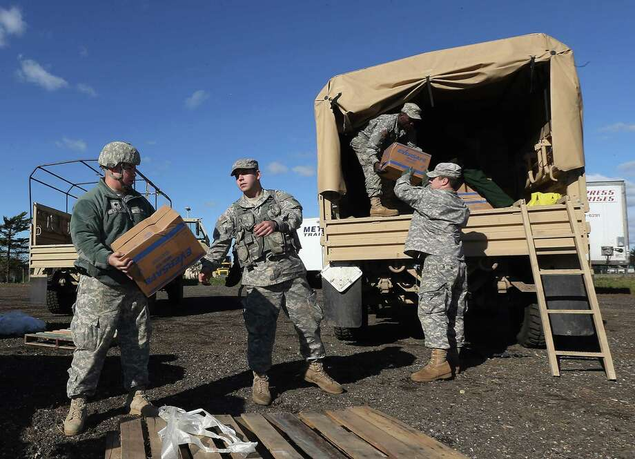 Army soldiers in New York pack food from FEMA on trucks in response to Superstorm Sandy.