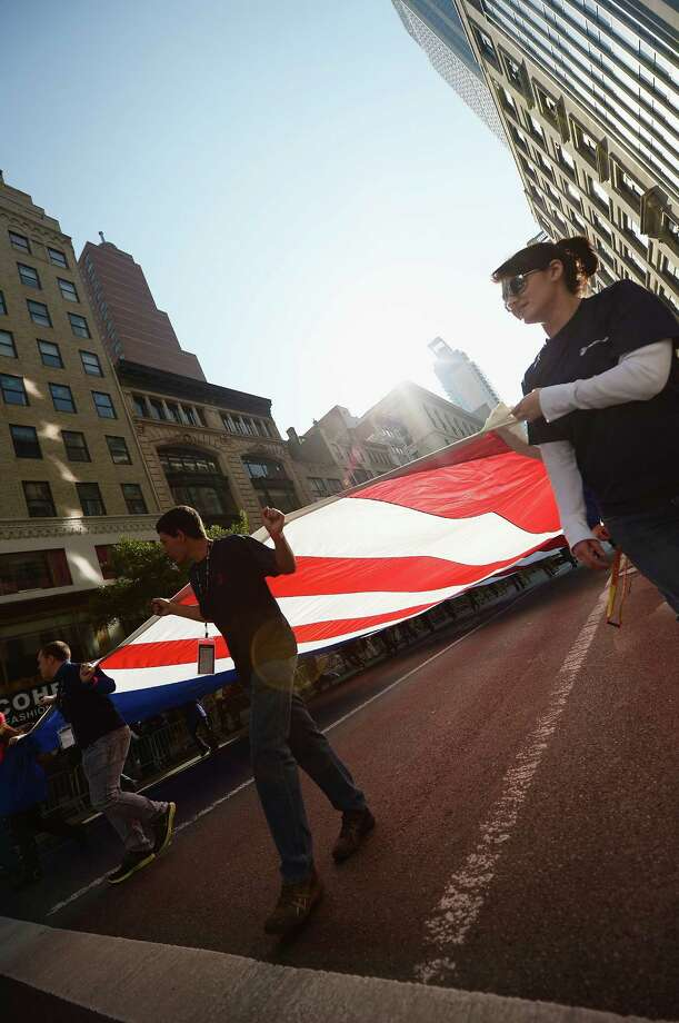 NEW YORK, NY - NOVEMBER 11:  Parade participants representing The Wounded Warriors Project carry the American flag, made in South Boston, Virginia on November 11, 2012 in New York City. Former Mayor Ed Koch is the grand marshal for the parade, which expects to draw thousands of spectators and is the commemoration of the 50th anniversary of the start of the Vietnam War. Photo: Michael Loccisano, Getty Images / 2012 Getty Images