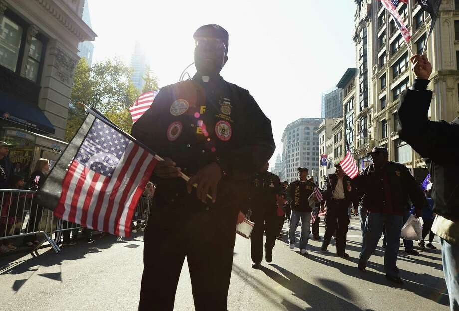 NEW YORK, NY - NOVEMBER 11: A Korean War Army Veteran turned Priest holds a POW MIA Flag and an American Flag while taking part in the Veteran's Day Parade on November 11, 2012 in New York City. Former Mayor Ed Koch is the grand marshal for the parade, which expects to draw thousands of spectators and is the commemoration of the 50th anniversary of the start of the Vietnam War. Photo: Michael Loccisano, Getty Images / 2012 Getty Images