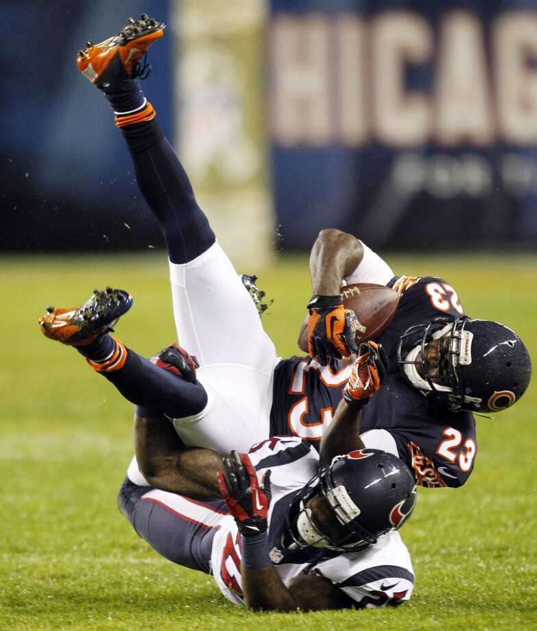 Bears wide receiver Devin Hester (23) is upended by Texans cornerback Kareem Jackson (25) during the second quarter. (Brett Coomer / Houston Chronicle)