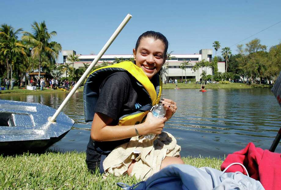 "Carolina Rivera smiles as she takes a rest after crossing the finish line during a ""Walk on Water"" event  at Florida International University in Miami, Thursday, Nov. 8, 2012. Students at FIU walked on water wearing water shoes they built as part of a class assignment on Thursday. Students must make it to the other side of a 175-foot lake on campus while wearing the aquatic shoes in order to get an ""A'' on the assignment, and the first student to do so wins $500. Photo: Alan Diaz, AP / AP"