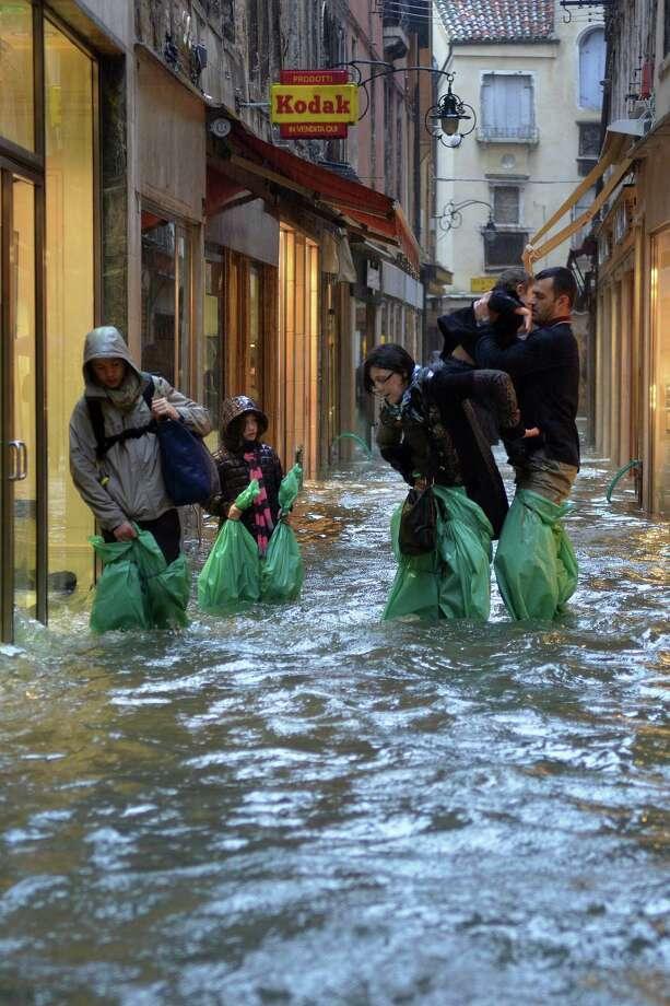 Parents carry their children in a small street during a 'acqua alta' on November 11, 2012 in Venice. Rain and wind hit the north of Italy on Sunday and the folooding reached 150 centimetres in Venice.  AFP PHOTO / MARCO SABADINMarco Sabadin,Marco Sabadin/AFP/Getty Images Photo: AFP, AFP/Getty Images / AFP