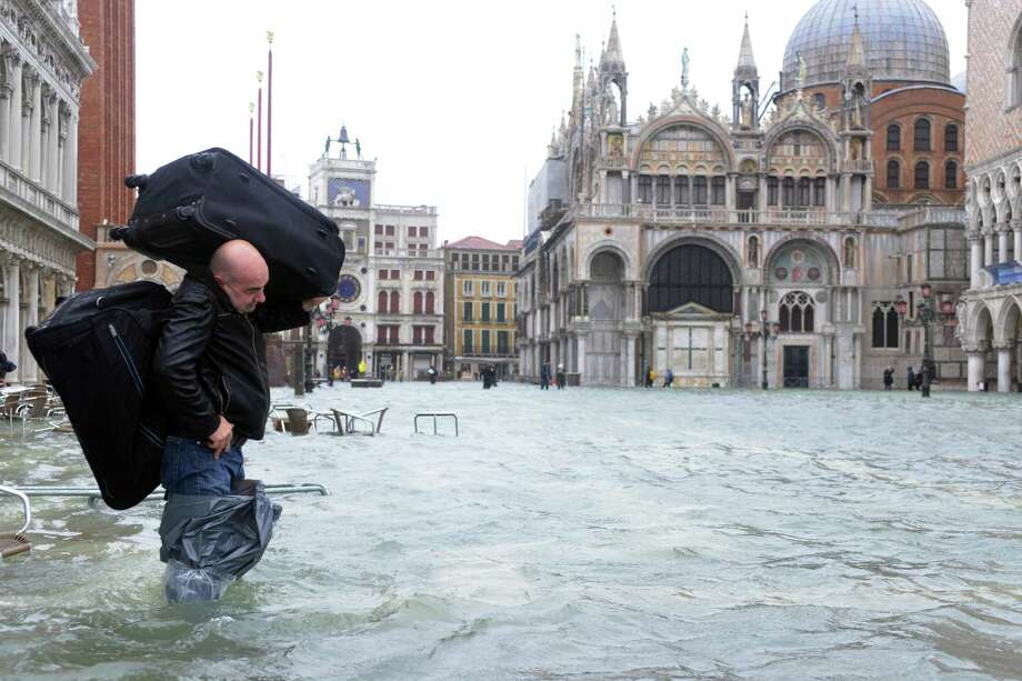 A man carries luggages on a flooded St Mark's square during a 'acqua alta' on November 11, 2012 in Venice. Rain and wind hit the north of Italy on Sunday and the folooding reached 150 centimetres in Venice.  AFP PHOTO / MARCO SABADINMarco Sabadin/AFP/Getty Images Photo: MARCO SABADIN, AFP/Getty Images / AFP