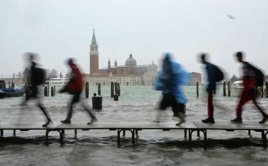 Tourists walk on footbridges during a 'acqua alta' on November 11, 2012 in Venice. Rain and wind hit the north of Italy on Sunday and the folooding reached 150 centimetres in Venice.  AFP PHOTO / MARCO SABADINMarco Sabadin,Marco Sabadin/AFP/Getty Images Photo: AFP, AFP/Getty Images / AFP
