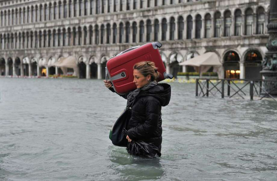 A tourist crosses flooded St. Mark's Square in Venice, Italy, Sunday, Nov. 11, 2012. High tides have flooded Venice, leading Venetians and tourists to don high boots and use wooden walkways to cross St. Mark's Square and other areas under water. Flooding is common this time of year and Sunday's level that reached a peak of 58.66 inches (149 centimeters) was below the 63 inches (160 centimeters) recorded four years ago in the worst flooding in decades. Photo: Luigi Costantini, AP / AP