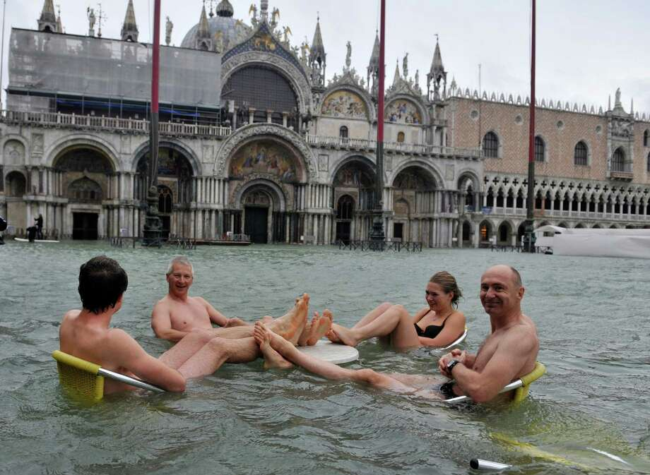 People sit at the table of a bar in a flooded St. Mark's Square in Venice, Italy, Sunday, Nov. 11, 2012. High tides have flooded Venice, leading Venetians and tourists to don high boots and use wooden walkways to cross St. Mark's Square and other areas under water. Flooding is common this time of year and Sunday's level that reached a peak of 58.66 inches (149 centimeters) was below the 63 inches (160 centimeters) recorded four years ago in the worst flooding in decades. Photo: Luigi Costantini, AP / AP