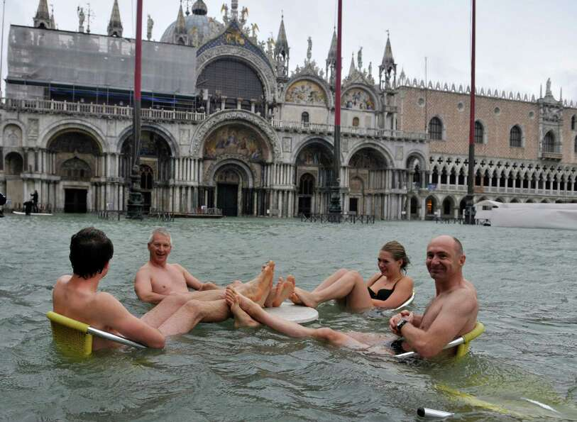 People sit at the table of a bar in a flooded St. Mark's Square in Venice, Italy, Sunday, Nov. 11, 2