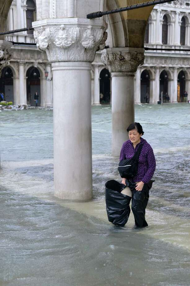 A woman walks on a flooded St Mark's square during a 'acqua alta' on November 11, 2012 in Venice. Rain and wind hit the north of Italy on Sunday and the folooding reached 150 centimetres in Venice.  AFP PHOTO / MARCO SABADINMarco Sabadin,Marco Sabadin/AFP/Getty Images Photo: AFP, AFP/Getty Images / AFP