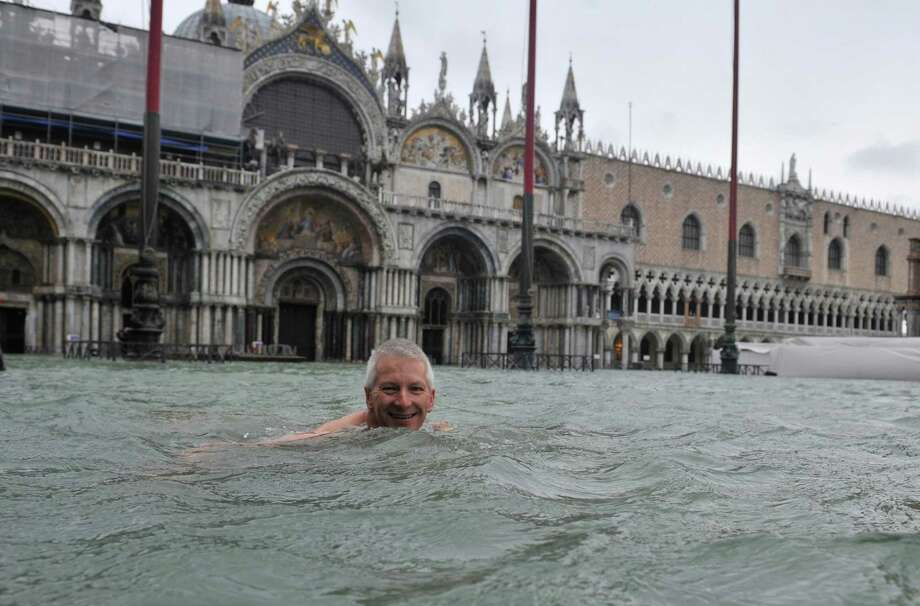 A man enjoys swimming in flooded St. Mark's Square in Venice, Italy, Sunday, Nov. 11, 2012. High tides have flooded Venice, leading Venetians and tourists to don high boots and use wooden walkways to cross St. Mark's Square and other areas under water. Flooding is common this time of year and Sunday's level that reached a peak of 58.66 inches (149 centimeters) was below the 63 inches (160 centimeters) recorded four years ago in the worst flooding in decades. Photo: Luigi Costantini, AP / AP
