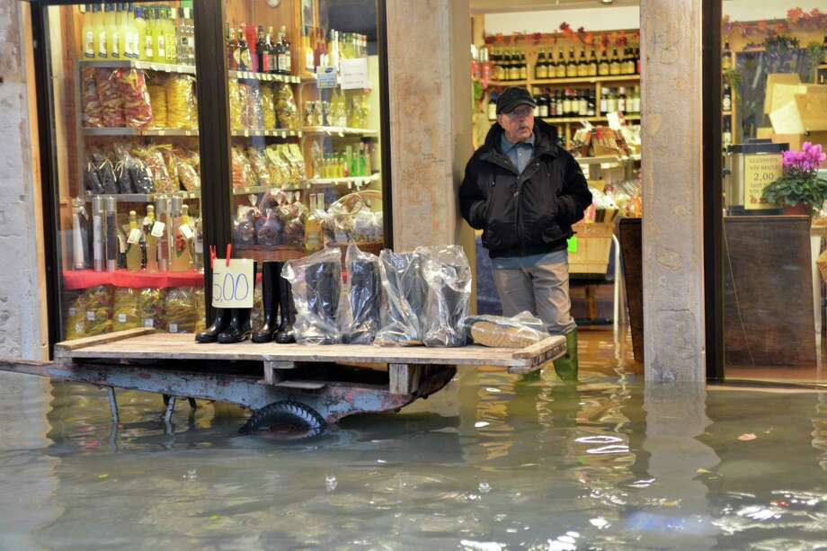 A shoes seller displays wellies outside his shop in a flooded street during a 'acqua alta' on November 11, 2012 in Venice. Rain and wind hit the north of Italy on Sunday and the folooding reached 150 centimetres in Venice.  AFP PHOTO / MARCO SABADINMarco Sabadin,Marco Sabadin/AFP/Getty Images Photo: AFP, AFP/Getty Images / AFP