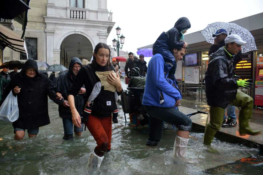 People walk in a flooded street during a 'acqua alta' on November 11, 2012 in Venice. Rain and wind hit the north of Italy on Sunday and the folooding reached 150 centimetres in Venice.  AFP PHOTO / MARCO SABADINMarco Sabadin,Marco Sabadin/AFP/Getty Images Photo: AFP, AFP/Getty Images / AFP