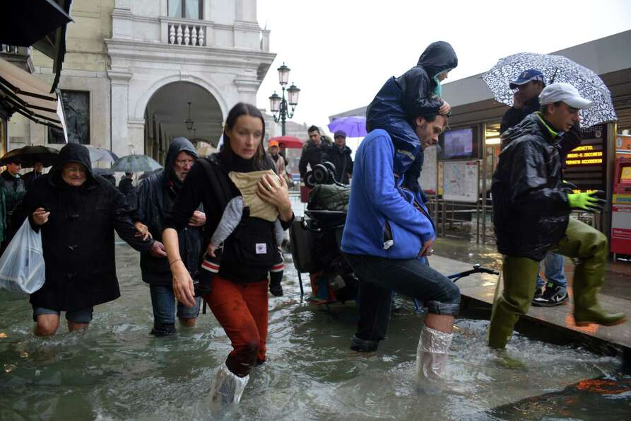 People walk in a flooded street during a 'acqua alta' on November 11, 2012 in Venice. Rain and wind