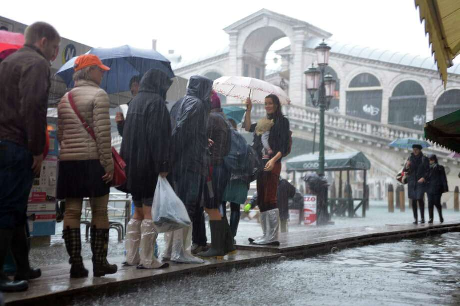 Tourists walk on footbridges near the Rialto bridge during a 'acqua alta' on November 11, 2012 in Venice. Rain and wind hit the north of Italy on Sunday and the folooding reached 150 centimetres in Venice.  AFP PHOTO / MARCO SABADINMarco Sabadin,Marco Sabadin/AFP/Getty Images Photo: AFP, AFP/Getty Images / AFP