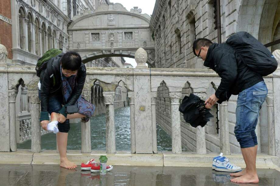 Tourists put on their shoes in front of the bridge of Sighs during a 'acqua alta' on November 11, 2012 in Venice. Rain and wind hit the north of Italy on Sunday and the folooding reached 150 centimetres in Venice.  AFP PHOTO / MARCO SABADINMarco Sabadin,Marco Sabadin/AFP/Getty Images Photo: AFP, AFP/Getty Images / AFP