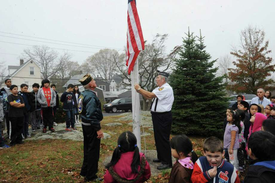 American Legion member John Zmarzlak, left, and Byram veteran Bob Lynagh, raise the flag at the ceremony at the New Lebanon School Salute to Veterans in Byram, Conn., Monday, Nov. 12, 2012. Photo: Helen Neafsey / Greenwich Time