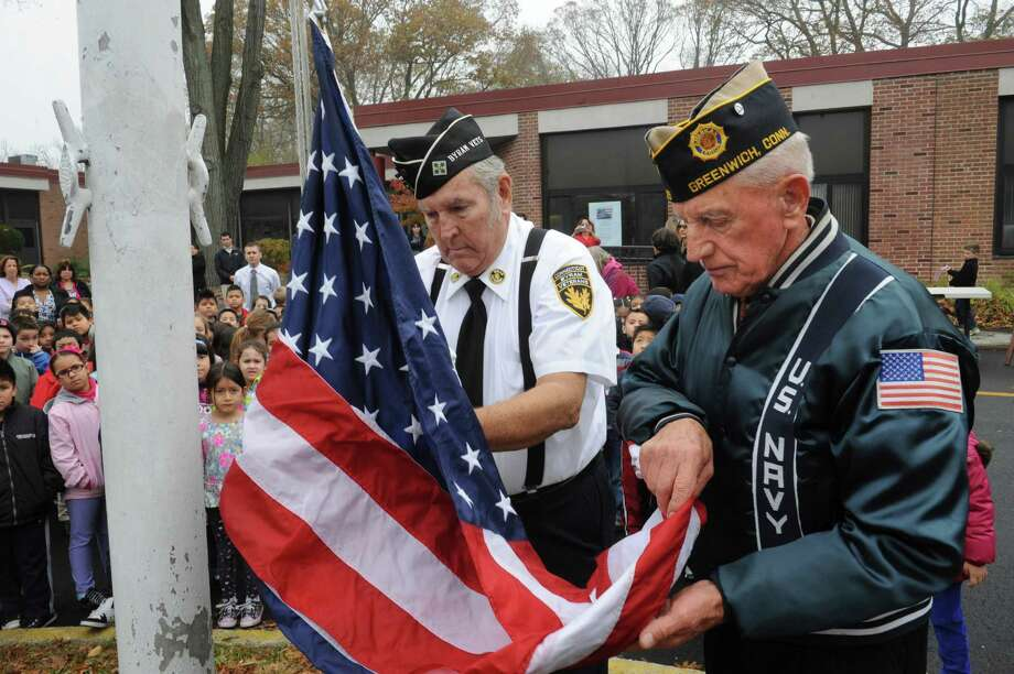 Byram veteran Bob Lynagh, left, and American Legion member John Zmarzlak raise the flag during the ceremony at the New Lebanon School Salute to Veterans in Byram, Conn., Monday, Nov. 12, 2012. Photo: Helen Neafsey / Greenwich Time
