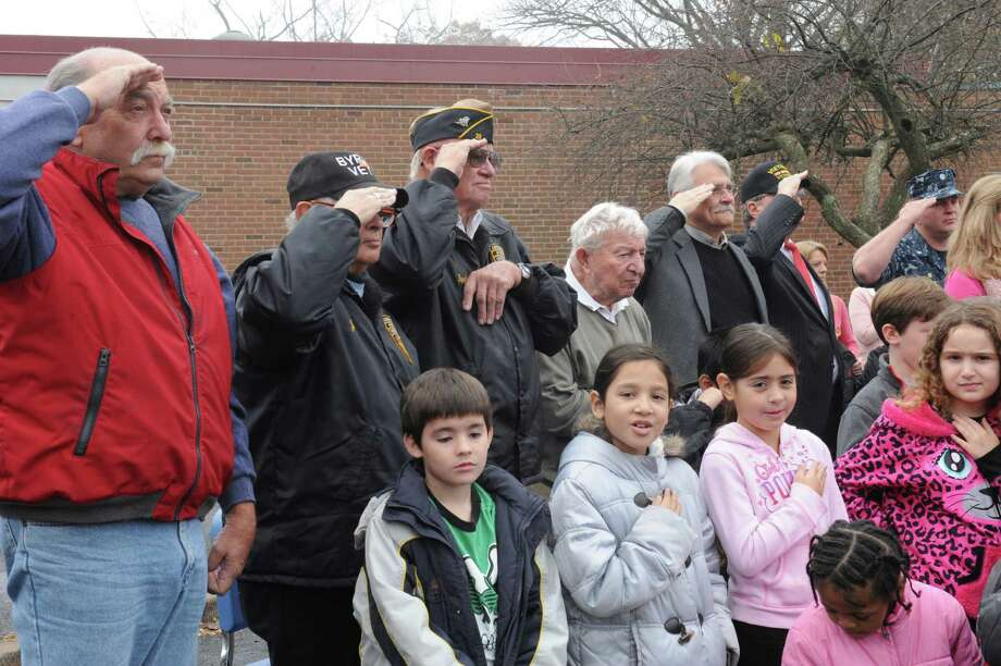 Frank Kasmarski, a veteran, left, salutes with other veterans at New Lebanon School's Salute to Veterans flag-raising ceremony in Byram, Conn., Monday, Nov. 12, 2012. Photo: Helen Neafsey / Greenwich Time