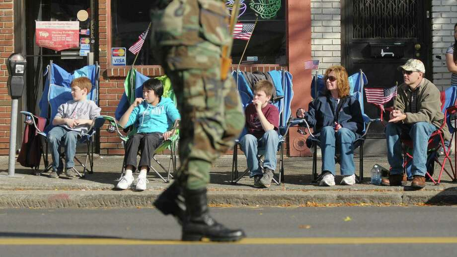 Members of the Gallagher family from Guilderland, from left to right, Kyle Gallagher, 8, Sophia Wu, 11, Jacob Gallagher, 11, Teresa Gallagher and her husband, Matt Gallagher, watch from their chairs as  the Albany Veterans Day Parade heads down Central Avenue on Monday, Nov. 12, 2012 in Albany, NY.   (Paul Buckowski / Times Union) Photo: Paul Buckowski