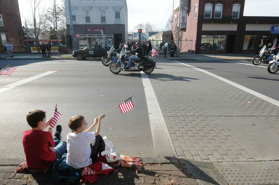 Evan Meashaw, 11, from Johnstown and Ryan Abatto, 9, from Clifton Park watch  the Albany Veterans Day Parade from a curb along Central Avenue on Monday, Nov. 12, 2012 in Albany, NY.   (Paul Buckowski / Times Union) Photo: Paul Buckowski