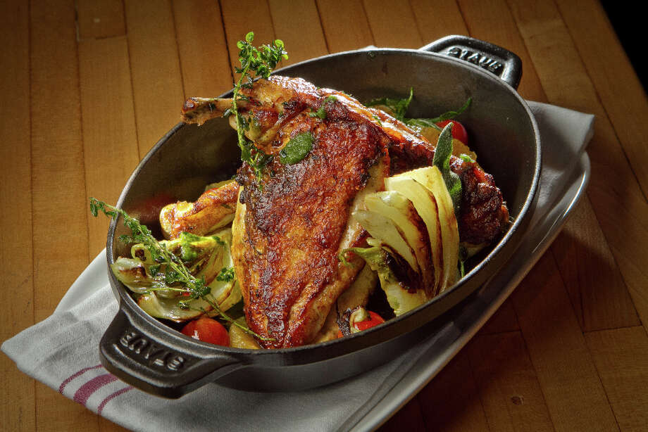 """Roasted half chicken ($24) is tucked into a cast-iron casserole and served on a cutting board with a napkin. It looks pretty, especially with the wedges of orange skin, charred fennel and whole cherry tomatoes, but it's difficult to eat and there is so much grease pooled in the bottom of the dish that the combination ends up tasting tired and sloppy."" Photo: John Storey, Special To The Chronicle / John Storey"