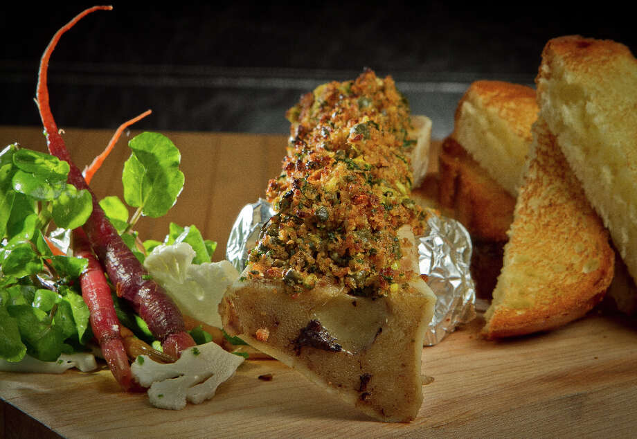 """Roasted bone marrow ($13) was also beautiful, with the Parmesan-crusted bone propped on a cutting board, a refreshing cauliflower and watercress mix and a stack of brioche toast; the problem was that the bread was dry, as if it were stale."" Photo: John Storey, Special To The Chronicle / John Storey"