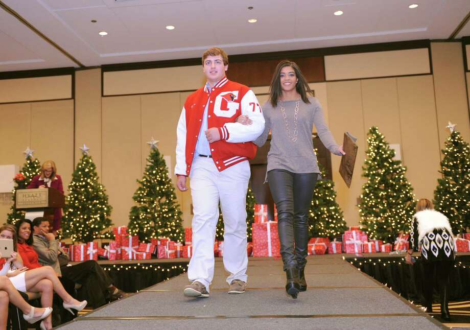 Seniors Bob Decker and Kendra Clarke at the sixth annual Holiday Boutique and Fashion Show to benefit  Greenwich High School cheerleading team at the Hyatt Regency Greenwich in Greenwich, Conn., Sunday, Nov. 11, 2012. Senior cheerleading members model while GHS football players escort the cheerleaders down the runway. Photo: Helen Neafsey / Greenwich Time