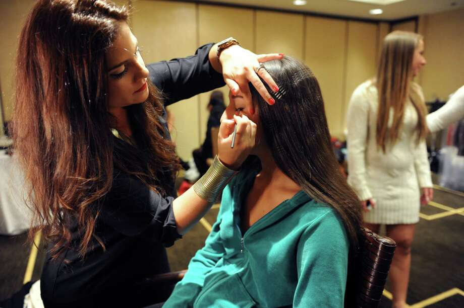 Judith Paniagua Tardio, makeup artist and hair stylist, left, working on Gabby DiLorenzo, a senior, at the sixth annual Holiday Boutique and Fashion Show to benefit  Greenwich High School cheerleading team at the Hyatt Regency Greenwich in Greenwich, Conn., Sunday, Nov. 11, 2012. Senior cheerleading members model while GHS football players escort the cheerleaders down the runway. Photo: Helen Neafsey / Greenwich Time