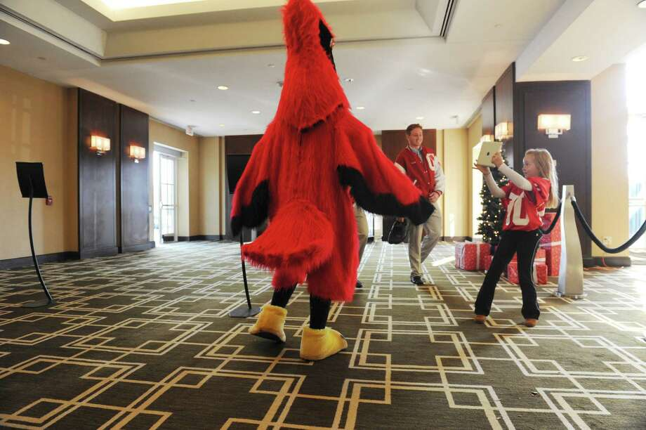 Kaitlin Kelly, 7, right, takes a picture of the cardinal at the sixth annual Holiday Boutique and Fashion Show to benefit  Greenwich High School cheerleading team at the Hyatt Regency Greenwich in Greenwich, Conn., Sunday, Nov. 11, 2012. Senior cheerleading members model while GHS football players escort the cheerleaders down the runway. Photo: Helen Neafsey / Greenwich Time