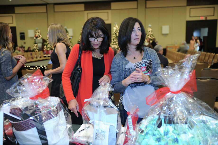 Leslie Salvatore, of Greenwich, left, and her sister Nancy Pinto, of Port Chester, shopping at the sixth annual Holiday Boutique and Fashion Show to benefit  Greenwich High School cheerleading team at the Hyatt Regency Greenwich in Greenwich, Conn., Sunday, Nov. 11, 2012. Senior cheerleading members model while GHS football players escort the cheerleaders down the runway. Photo: Helen Neafsey / Greenwich Time