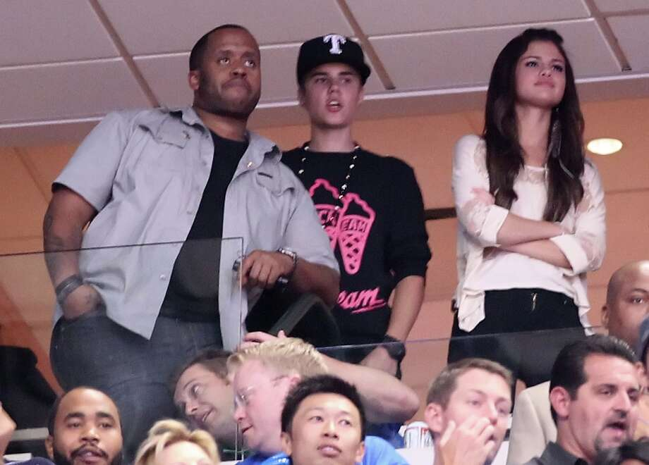 Kenny Hamilton and singers Justin Bieber and Selena Gomez attend Game Four of the 2011 NBA Finals between the Dallas Mavericks and the Miami Heat at American Airlines Center on June 7, 2011 in Dallas, Texas. Photo: Mike Ehrmann, Getty Images / 2011 Getty Images
