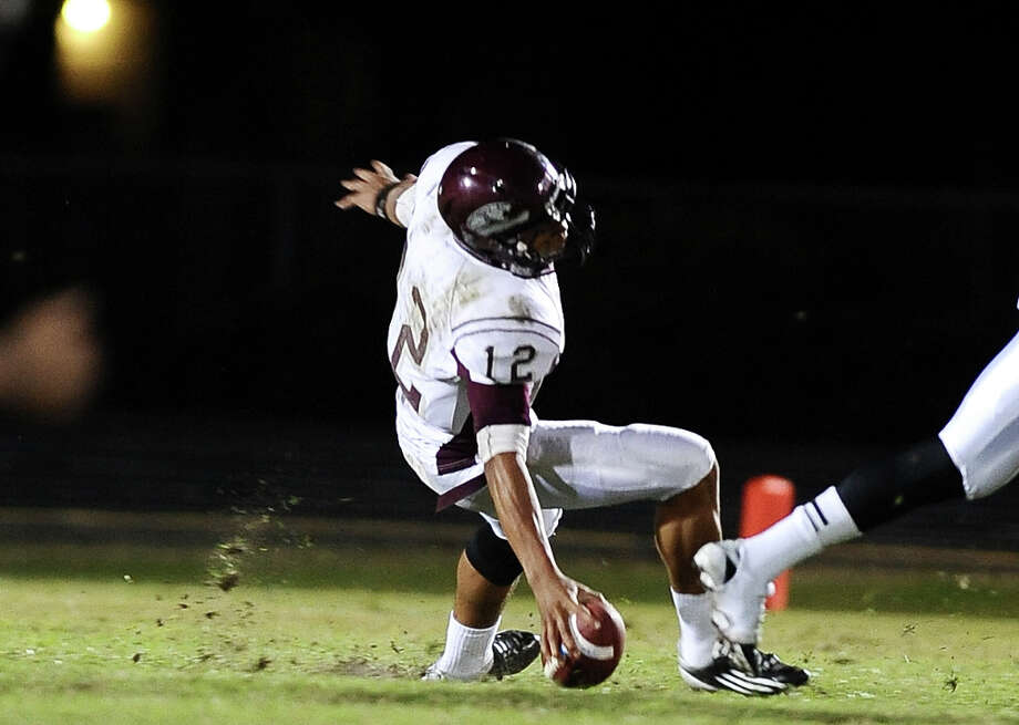 Central quarterback, Robert Mitchell, slips in the back field causing a fumble and an injury to himself during the Nederland High School football game against Central High School in Nederland on Friday, November 9, 2012.Photo taken:Randy Edwards/The Enterprise Photo: Randy Edwards